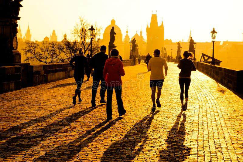 Löpareidrottsman nen har jogga genomkörare för morgon på Charles Bridge i Prague, Tjeckien Sund livsstil och aktiv royaltyfri fotografi