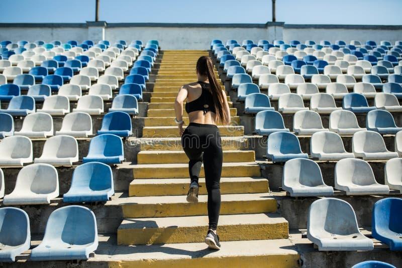 Löpareidrottsman nenspring på trappa Begrepp för wellness för genomkörare för kondition för ung kvinna jogga arkivfoton