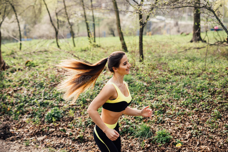 Löpareidrottsman nenspring på tropiskt parkerar begrepp för wellness för genomkörare för kvinnakondition jogga arkivfoto