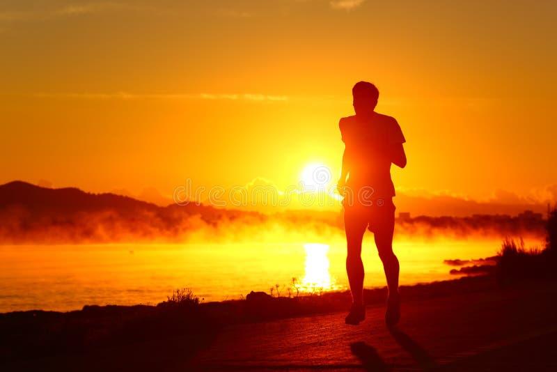 Löparekontur som kör på solnedgången på stranden royaltyfria bilder