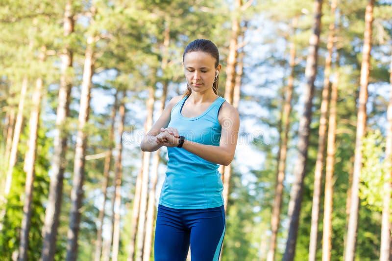 Löparekvinna med bildskärmen för hjärtahastighet för att köra i skog royaltyfri fotografi