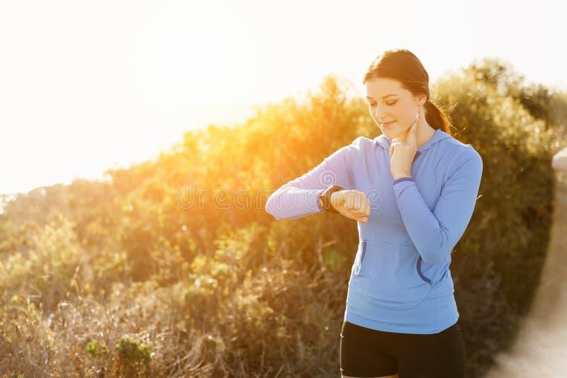 Löparekvinna med spring för bildskärm för hjärtahastighet på stranden arkivbilder