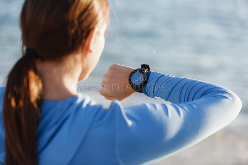 Löparekvinna med spring för bildskärm för hjärtahastighet på stranden royaltyfri fotografi