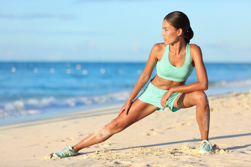 Löparekvinnan som sträcker ben med benet för övningen för utfallknäsenaelasticiteten, sträcker arkivfoto