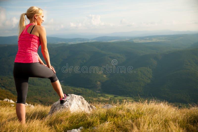 Löparekvinnan vilar på en bergöverkant efter rinnande genomkörare arkivfoton