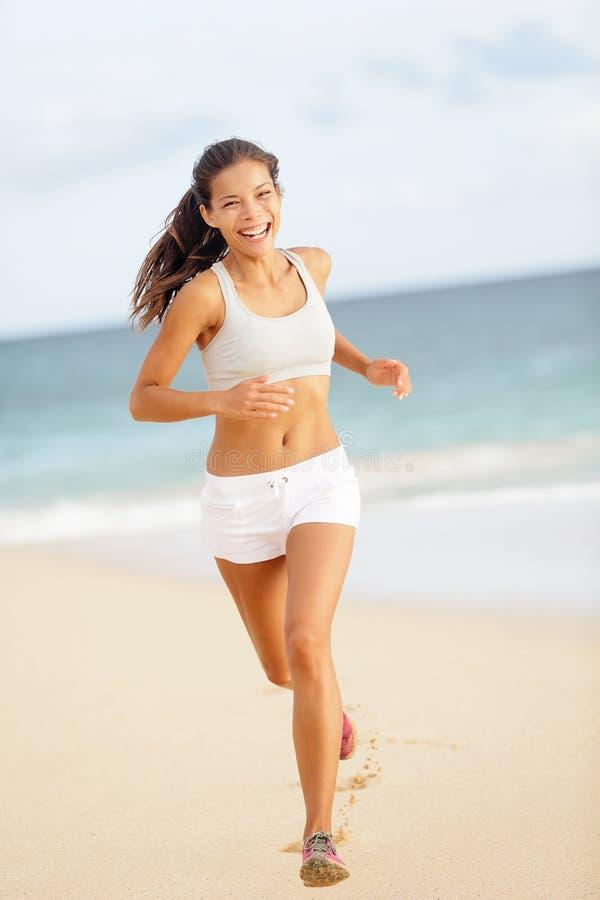 Löparekvinnaspring på att le för strand som är lyckligt royaltyfria foton