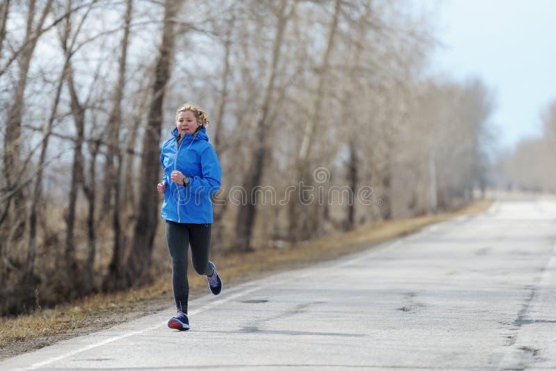 Löparekvinnaspring på vägen i härlig natur Jogga traini royaltyfri bild