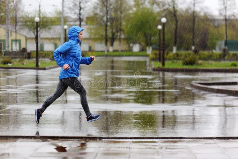 Löparekvinnaspring parkerar in i regnet Jogga utbildning för M royaltyfri foto