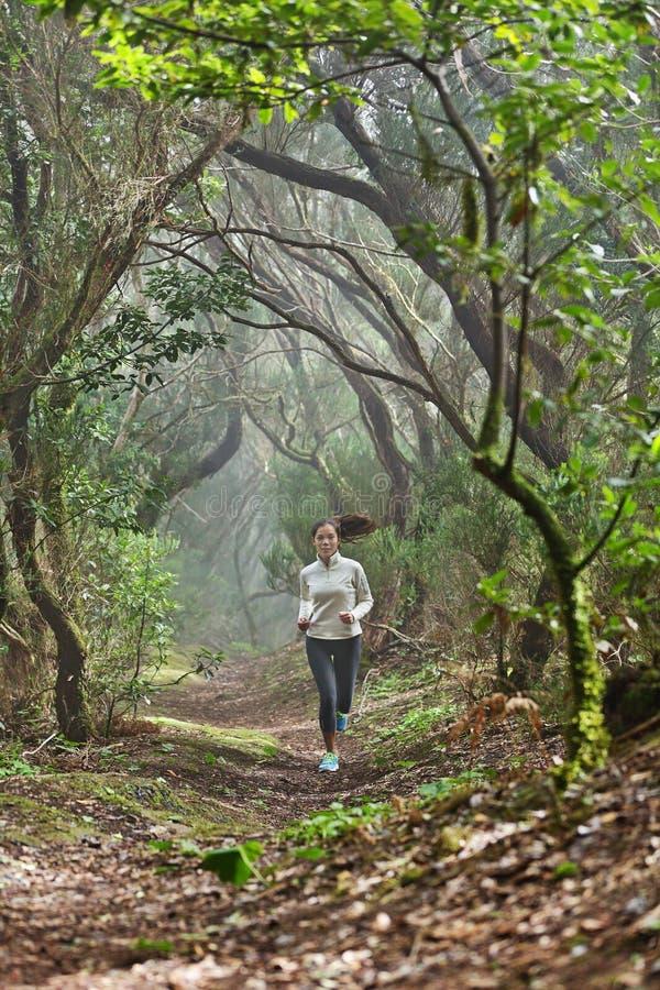 Löparekvinnaterränglöpning i skog royaltyfri foto