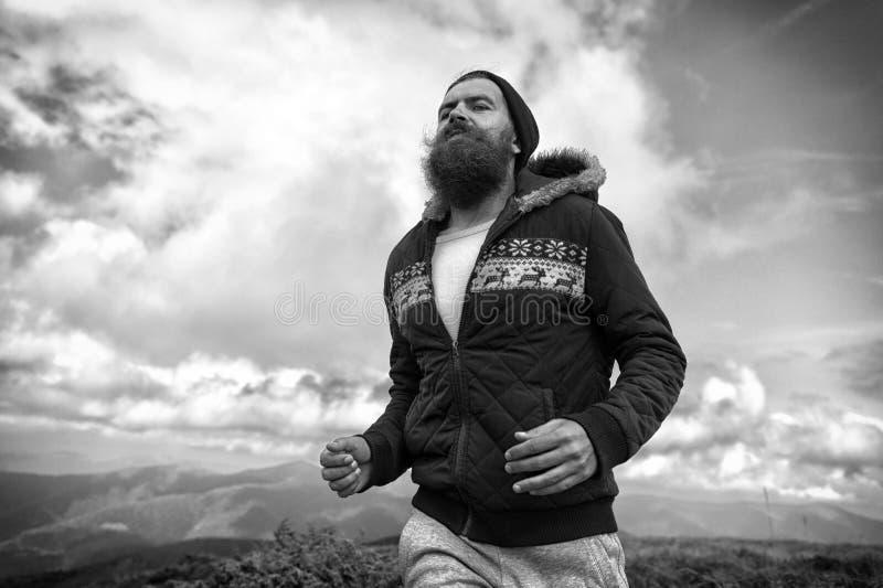 Löpareman med lång skäggkörning på berglandskap arkivbilder