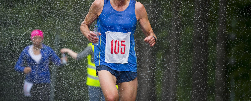 Löpareman som kör under maraton för regndroppstad fotografering för bildbyråer