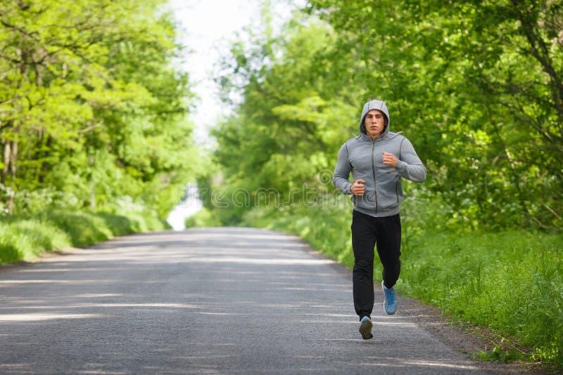 Löparemanspring på vägutbildning sprintar Sportslig man kört utarbeta utanför arkivbilder
