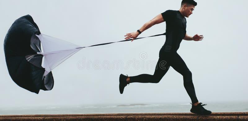 Löparen som utarbetar genom att använda motstånd, hoppa fallskärm royaltyfri fotografi