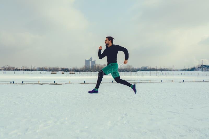 Löparespring på snö och se rakt framåt arkivfoton