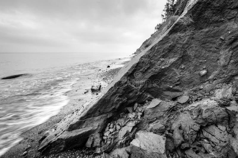 Lös strand-, havs- och klippaerosion i vinter svart white royaltyfri bild