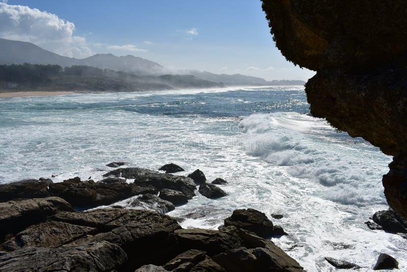 Lös strand och hav från en klippa Stora vågor som bryter mot, vaggar, för skum och för mist den soliga dagen, blå himmel, Galicia royaltyfri fotografi