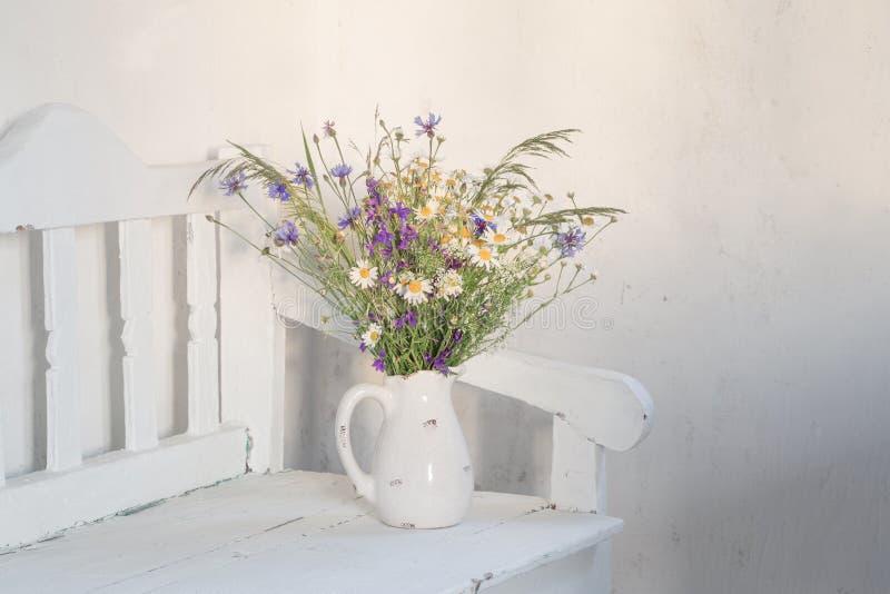 Lösa blommor i tillbringare på den vita träbänken arkivfoton