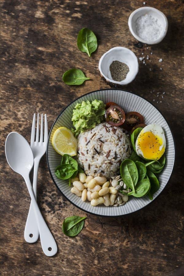 Lösa ris, kokt ägg, spenat, avokadopuré, bönor, tomatbuddha bunke på träbakgrund, bästa sikt sund vegetarian för mat arkivfoto