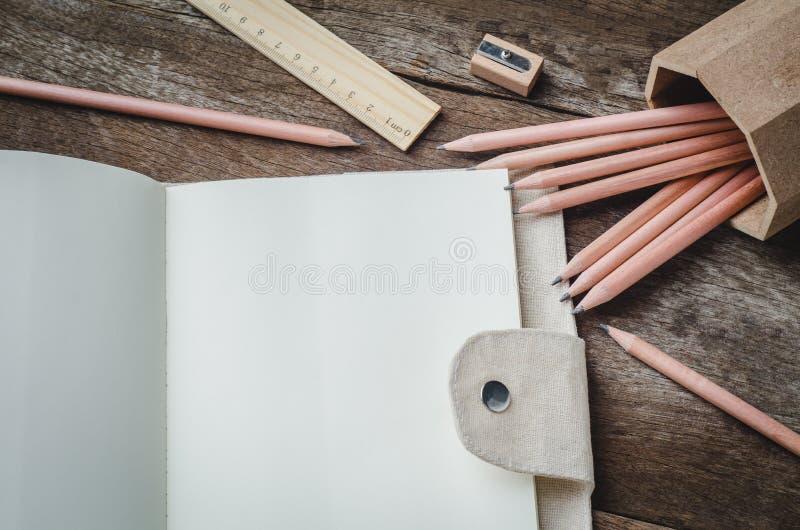 Löschen Sie tägliches Planernotizbuch mit Bleistiften, Bleistiftspitzer und lizenzfreie stockfotos