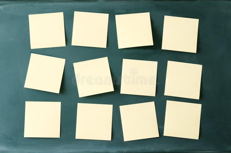 Löschen Sie viele klebrigen Anmerkungen, die zur Tafel befestigt werden lizenzfreie stockbilder