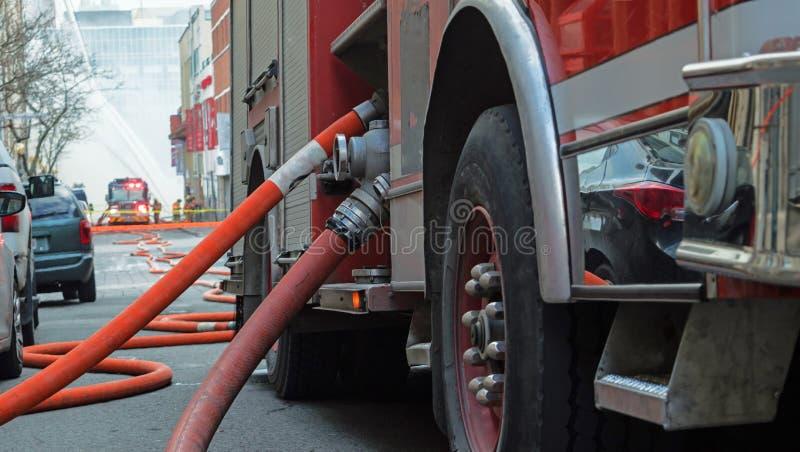 Löschfahrzeug in der Aktion mit Feuerwehrmännern und Feuer im Hintergrund lizenzfreies stockbild