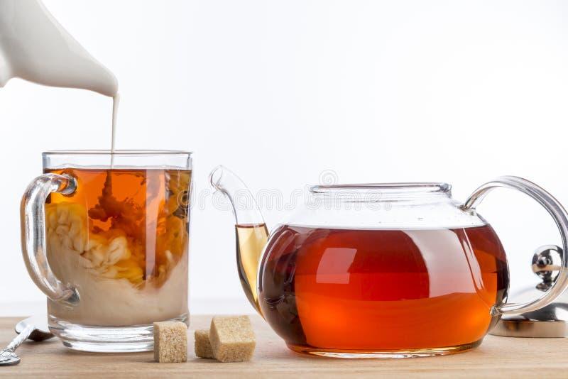Lösen Sie Milch in einer Schale schwarzem Tee auf stockbild