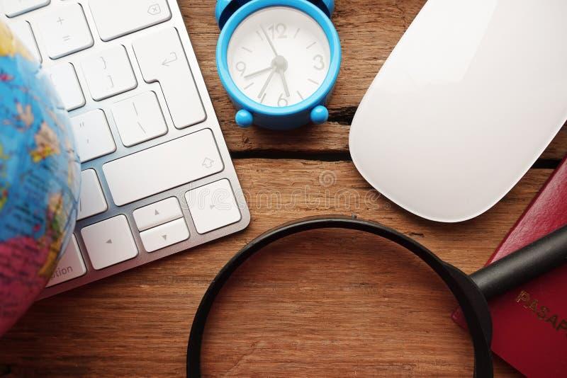 Lösen Sie Planungskonzept mit Reisegegenständen auf dem Schreibtisch aus, um on-line-Reservierung für Flüge und Unterkunft anzubr lizenzfreie stockfotografie