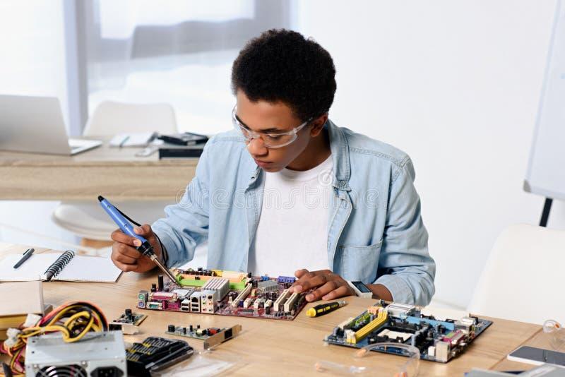 lötende Rechnerschaltung des Afroamerikanerjugendlichen mit Lötkolben stockfotos