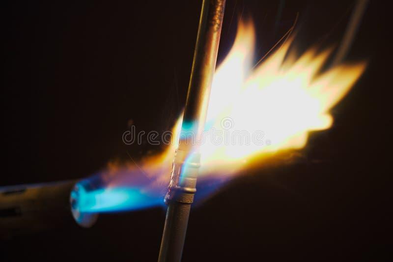 Lötlampe-Flamme und Kupfer-Rohr lizenzfreie stockfotos