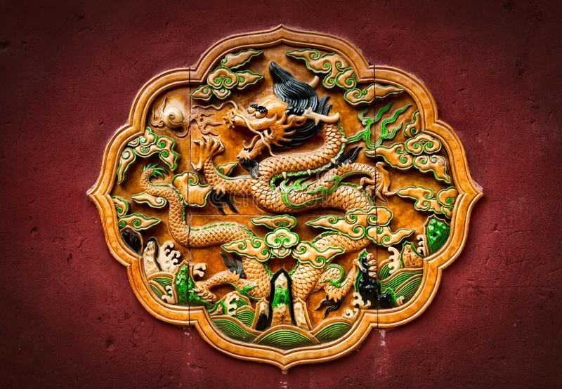 Lövsågsarbete i form av en drake på den röda väggen i Forbiddenet City Beijing royaltyfri fotografi
