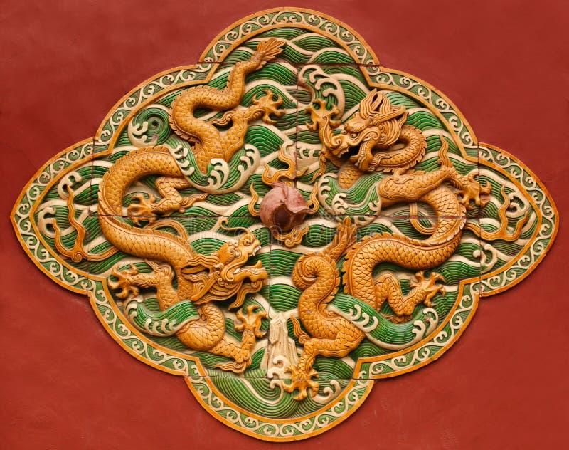 Lövsågsarbete i form av en drake på den röda väggen i Forbiddenet City Beijing royaltyfria foton