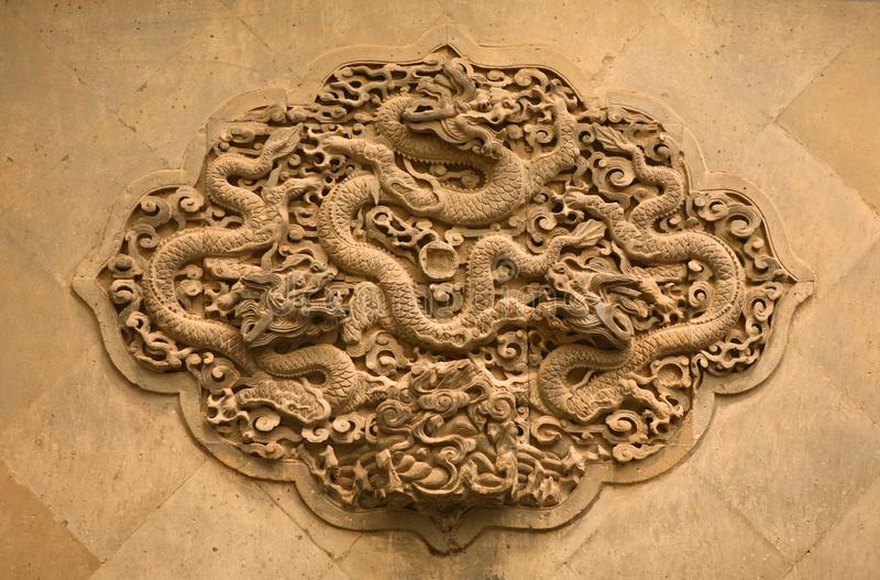 Lövsågsarbete i form av en drake på väggen i Forbiddenet City Peking, royaltyfri fotografi