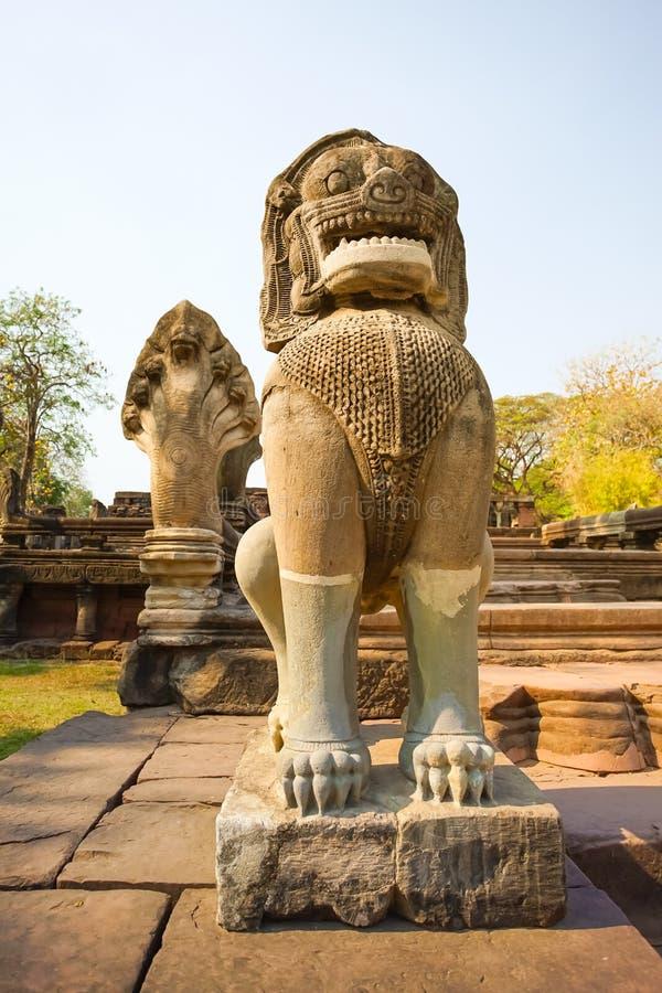 Löwe- oder Singha- und Nagasandsteinstatue in Prasat Hin Phimai stockbilder