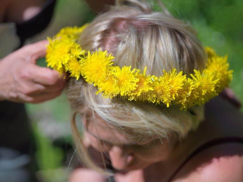 Löwenzahngirlande auf einem blonden Frauenkopf lizenzfreie stockfotos