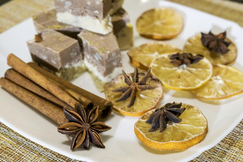 Lüge auf einer Platte von Kuchen, von Scheiben einer Zitrone mit Sternanis und von Zimtstangen lizenzfreies stockbild
