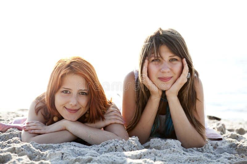 Lüge mit zwei schöne Mädchen auf dem Strand. lizenzfreie stockfotografie