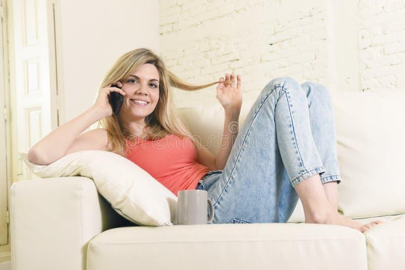 Lügen der jungen Frau bequem auf der Hauptsofacouch, die auf dem Handylächeln glücklich spricht lizenzfreie stockfotos