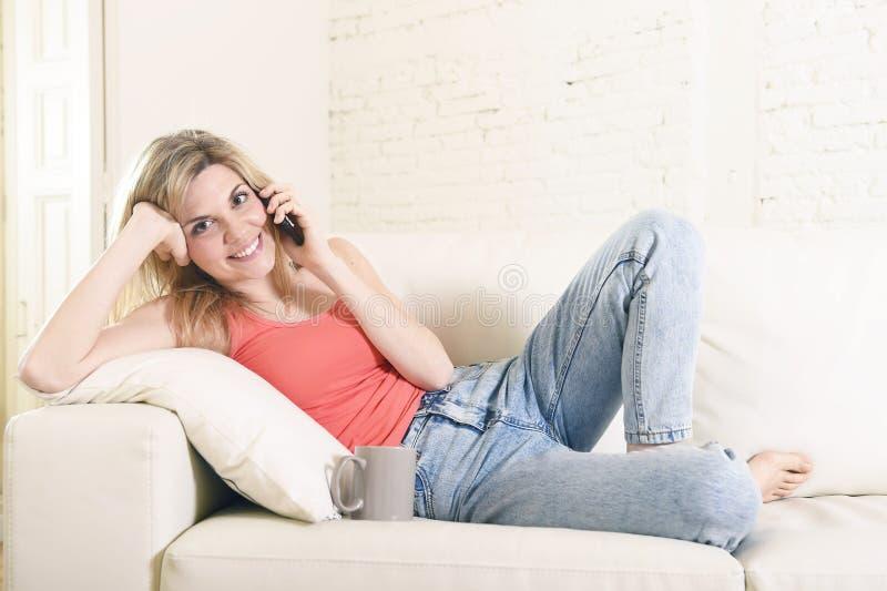 Lügen der jungen Frau bequem auf der Hauptsofacouch, die auf dem Handylächeln glücklich spricht stockbilder