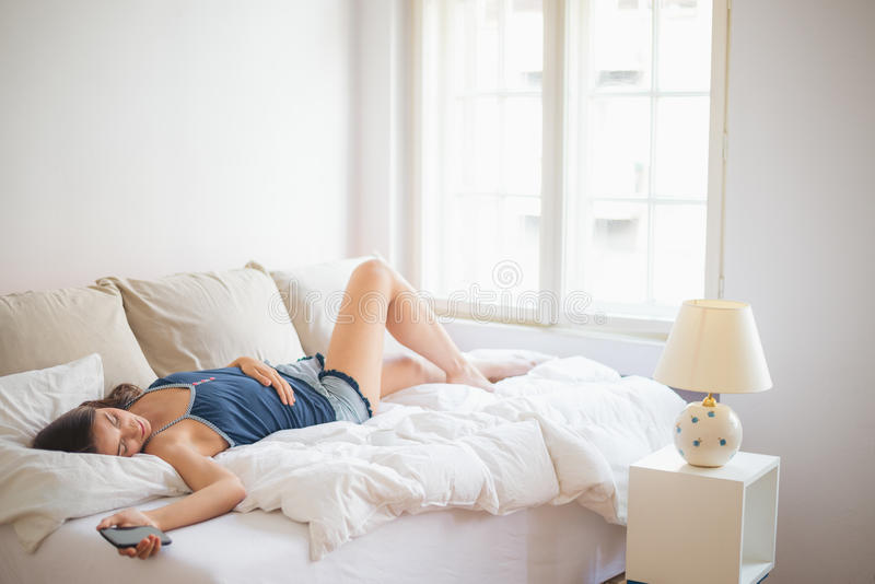 Lügen im Bett und Halten des Handys stockbilder