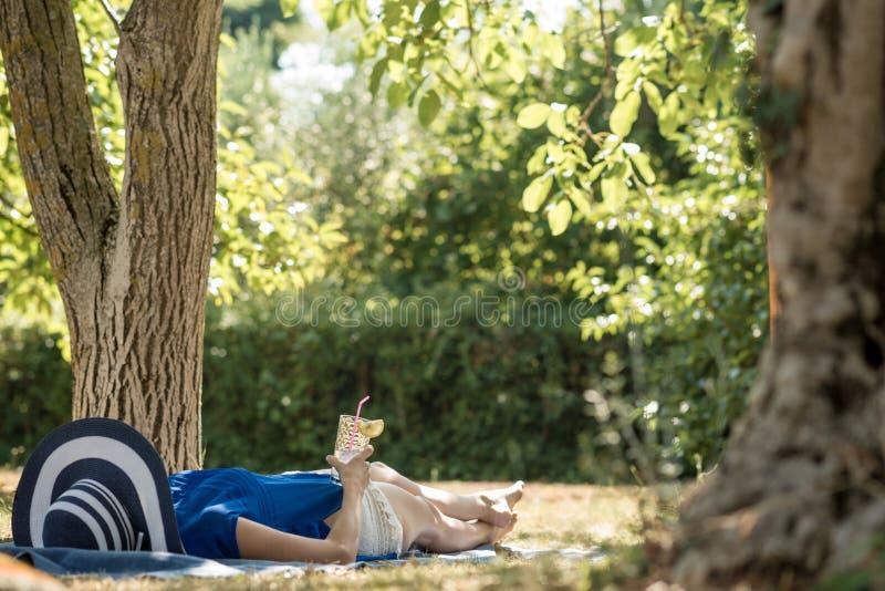 Lügenentspannung der Frau im Schatten eines Baums in einem Garten stockfotos