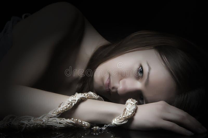 Lügenfrau mit einem Armband auf ihrem Arm lizenzfreie stockfotografie