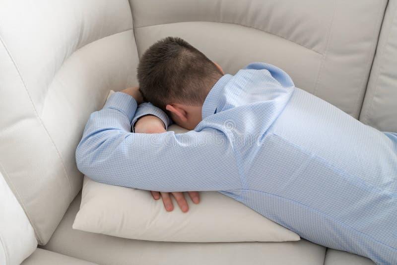 Lügengesicht des deprimierten Jugendlichen unten auf Sofa stockbild