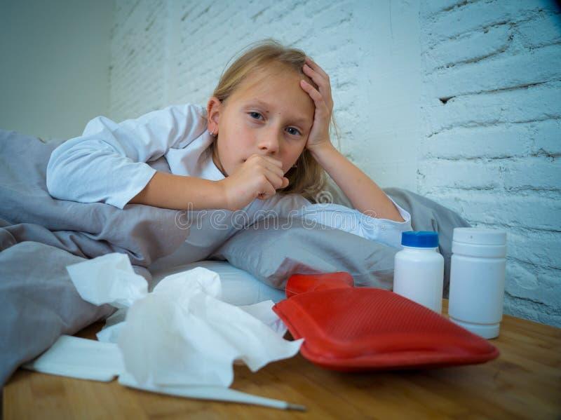 Lügenkranker des kleinen Mädchens im Bett das Fühlen hustend krank mit dem hohen Fieber, das eine kalte Grippe hat stockbilder
