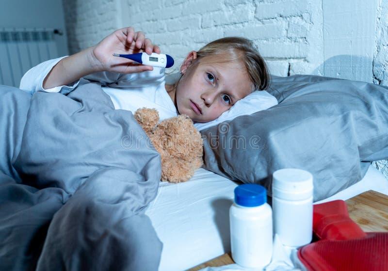 Lügenkranker des kleinen Mädchens im Bett das Thermometergefühl krank mit dem hohen Fieber überprüfend, das eine kalte Grippe hat lizenzfreies stockfoto