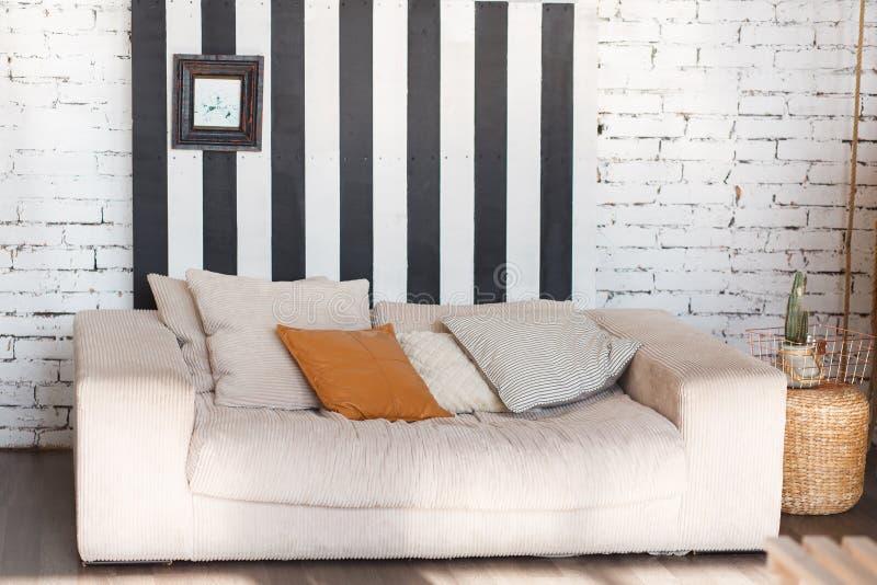 Lüpfen Sie modernen Innenraum mit weißer Backsteinmauer, schwarzen Streifen und Sofa in der Front lizenzfreie stockfotos