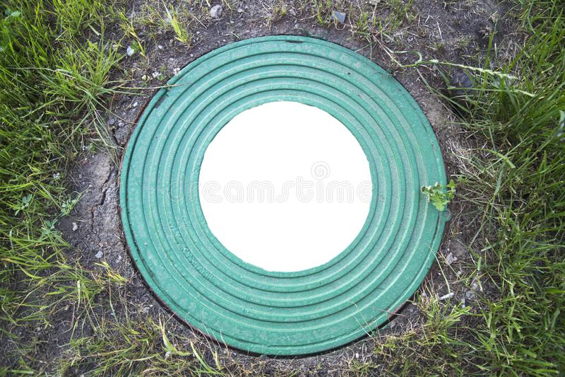 Ląg dobrze ciska żelaznego ciężkiego turkus z wzorem wiele pierścionki na tle zielona trawa W centrum round biel fotografia stock