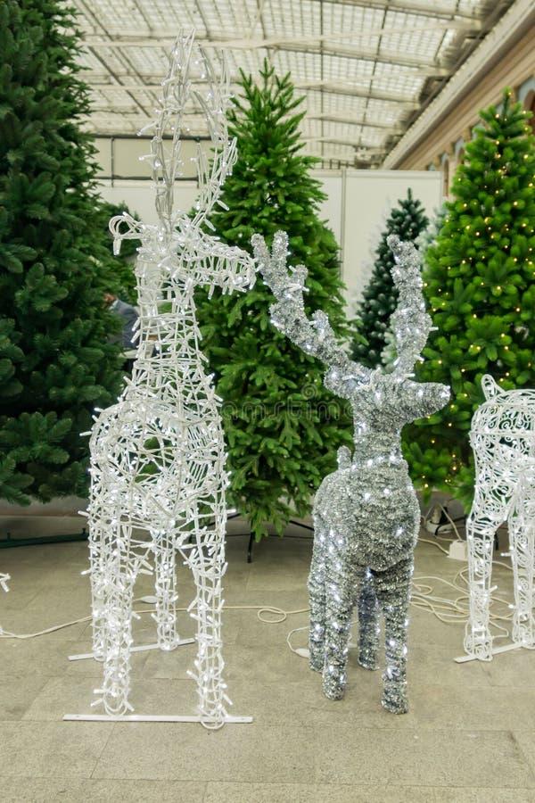 Lśniące renifery wykonane z drutów i żarówek na drzewach świątecznych w tle do sprzedaży obraz royalty free