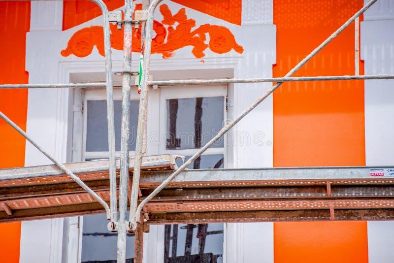 L'échafaudage du peintre avec la maison orange à l'arrière-plan photo libre de droits