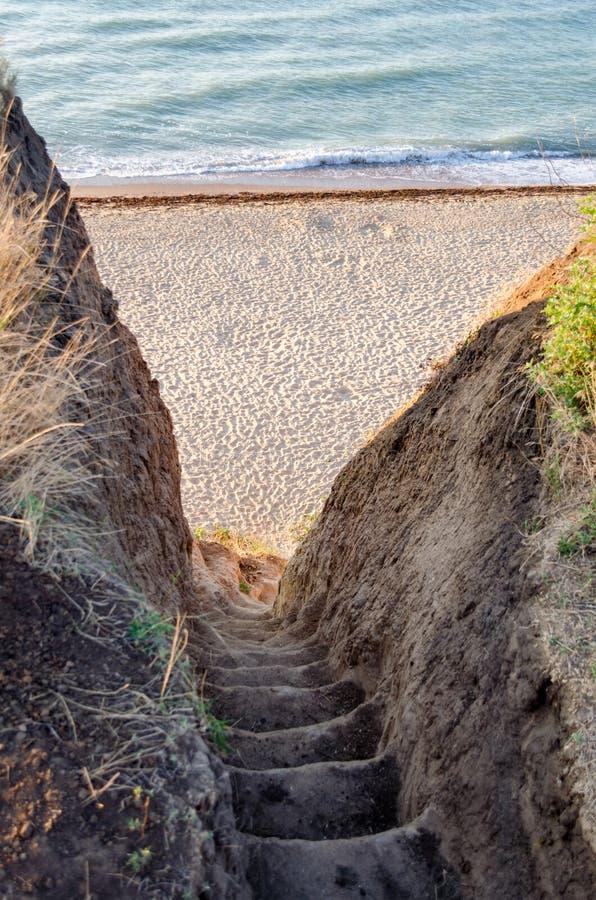 L'échelle a excavé sur une falaise menant à la plage et à la mer bleue images libres de droits