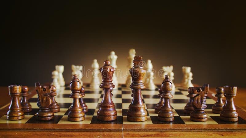 L'échiquier avec les chiffres en bois, des échecs noirs figure sur le premier plan photographie stock